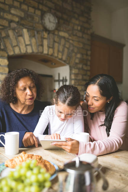 Family using digital tablet on dining table at home — Stock Photo