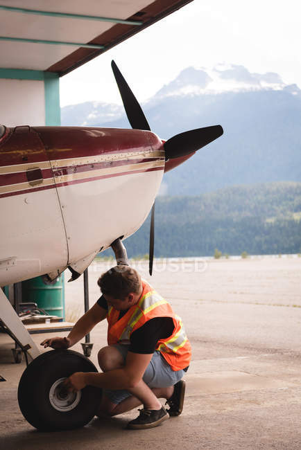 Механик, обслуживание самолетов шасси на аэрокосмической ангар — стоковое фото