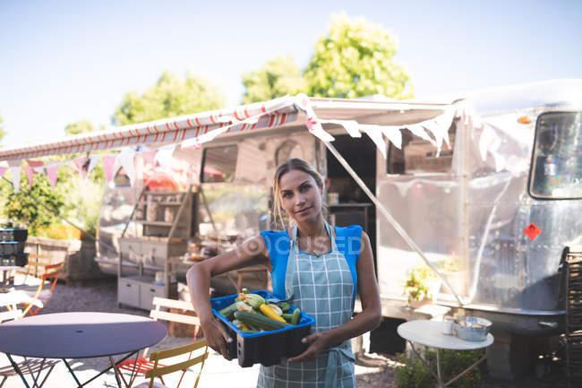 Жіночий офіціантка проведення овочі в кошик поблизу харчової вантажівка — стокове фото