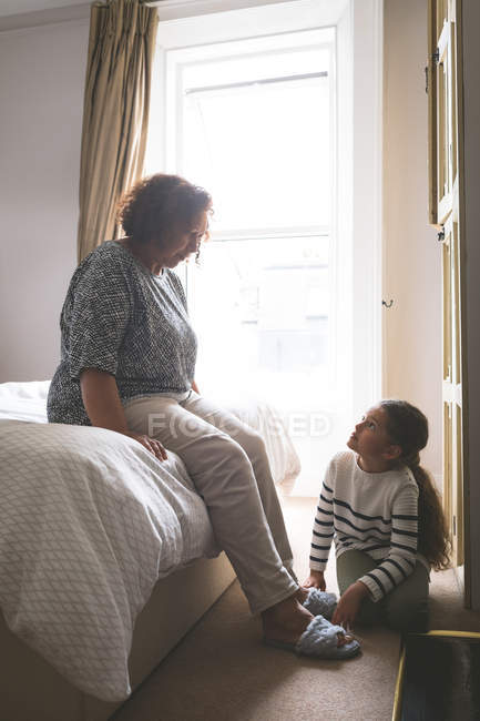 Granddaughter helping grandmother to wear slipper at home — Stock Photo