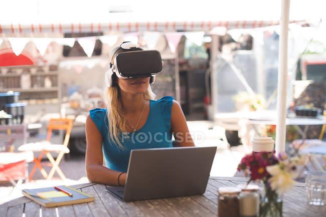Жінка за допомогою віртуальної реальності гарнітура з ноутбуком в придорожньому кафе — стокове фото