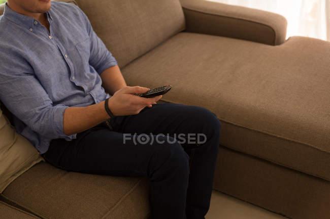 Metà sezione di uomo cambiando i canali in soggiorno a casa — Foto stock