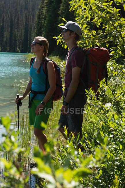 Пара стоящих возле реки в солнечный день — стоковое фото