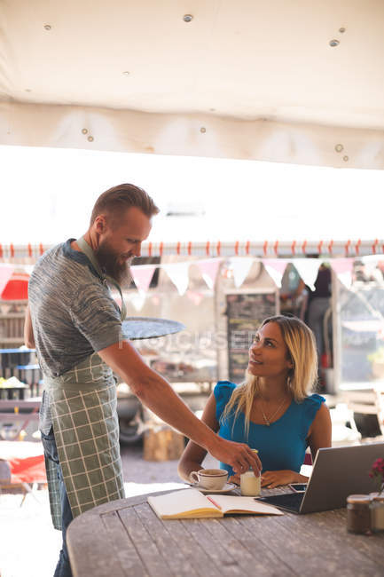 Male waiter serving breakfast to female customer in outdoor cafe — Stock Photo