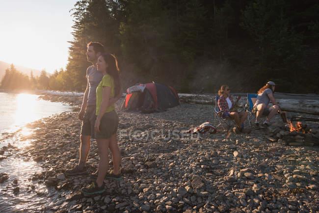 Пара стоя возле реки — стоковое фото
