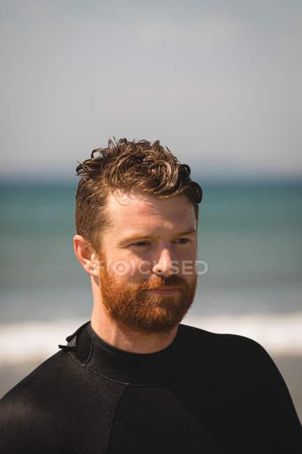Закри серфер, стоячи на пляжі — стокове фото