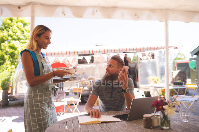 Female waiter serving coffee to male customer in outdoor cafe — Stock Photo
