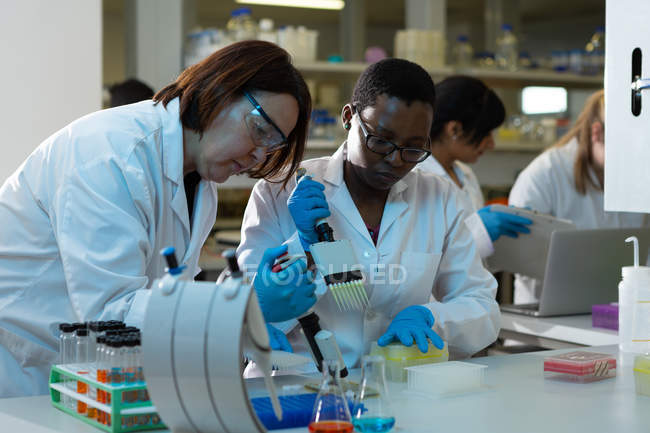 Female scientists using pipette together in laboratory — Stock Photo