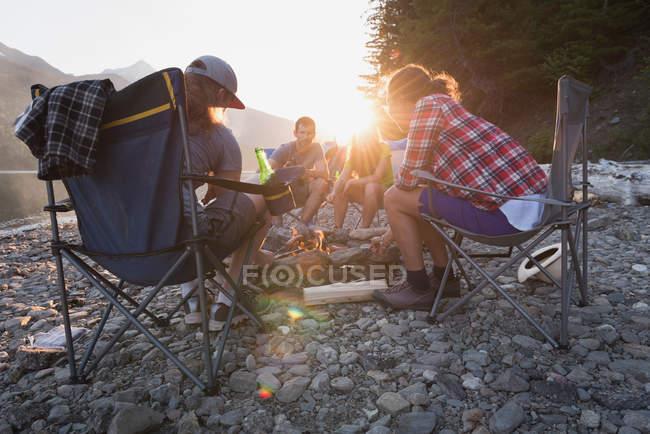 Група друзів випалу хот-доги на вогнищі в горах — стокове фото