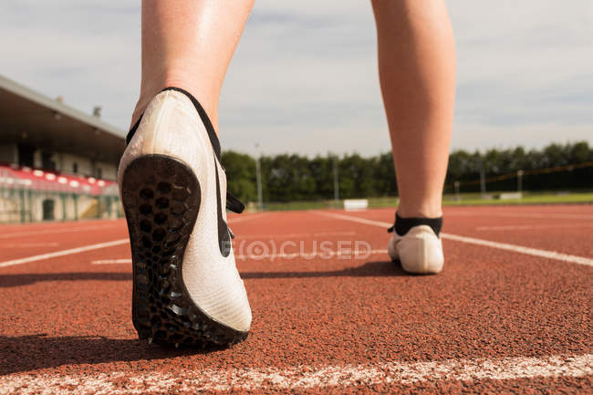 Close-up of female athletic standing on running track — Stock Photo