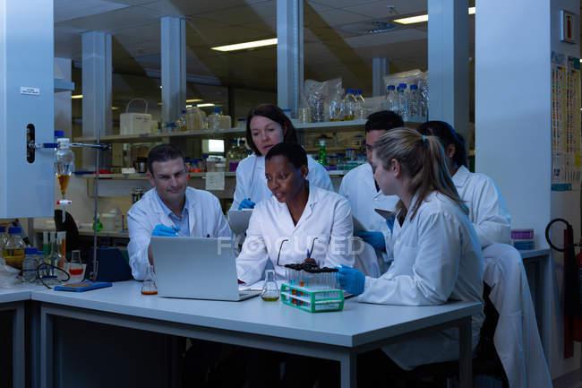 Equipe de cientista usando laptop juntos no laboratório — Fotografia de Stock