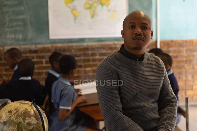 Чоловічий вчителя розслаблюючій в класі в школі — стокове фото