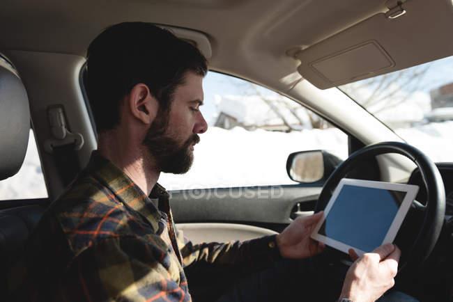 Uomo che utilizza tablet digitale in auto durante l'inverno — Foto stock