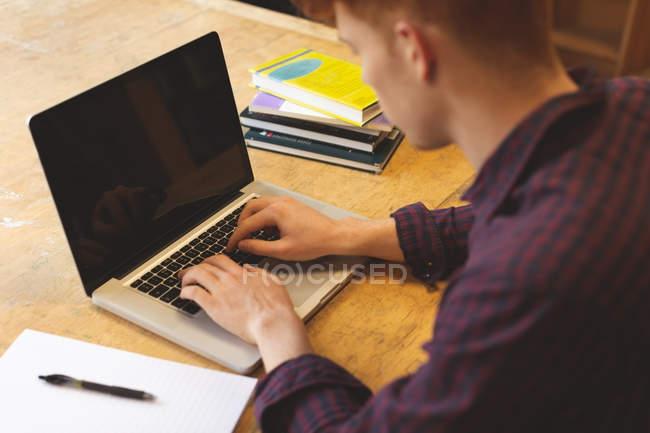 Visão de alto ângulo do estudante universitário usando laptop na biblioteca — Fotografia de Stock