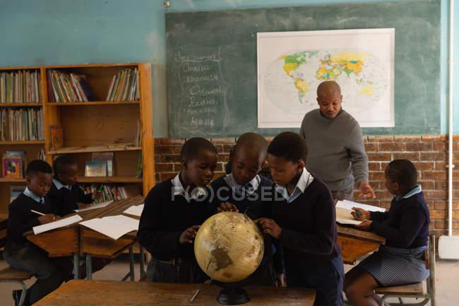 Школьники используют глобус в классе в школе — стоковое фото