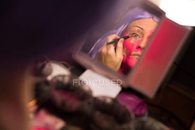 Женщина, живопись ее лицо с щеткой для празднования Хэллоуина — стоковое фото