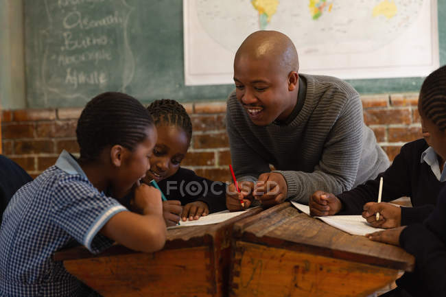 Male teacher teaching students in the classroom at school — Stock Photo