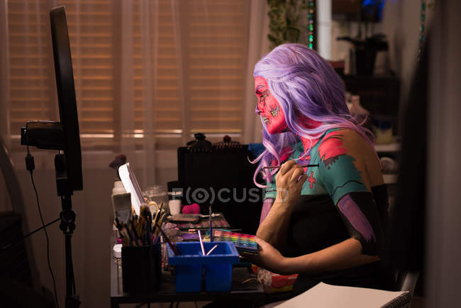 Woman painting her body for halloween celebration — Stock Photo