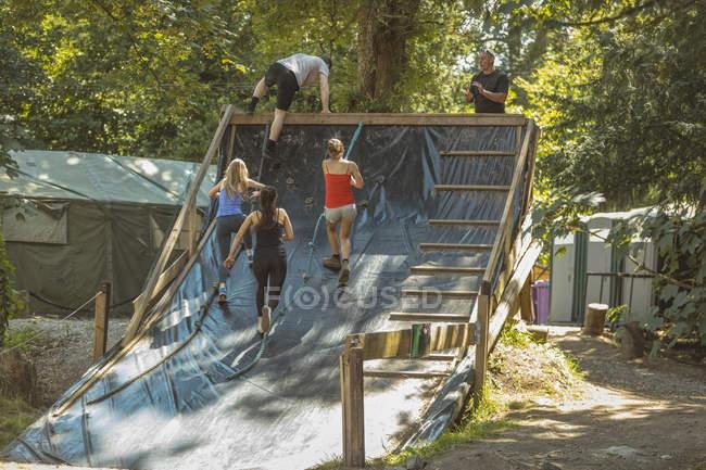 Encaixe o treinamento dos povos sobre o curso de obstáculo no acampamento da bota — Fotografia de Stock