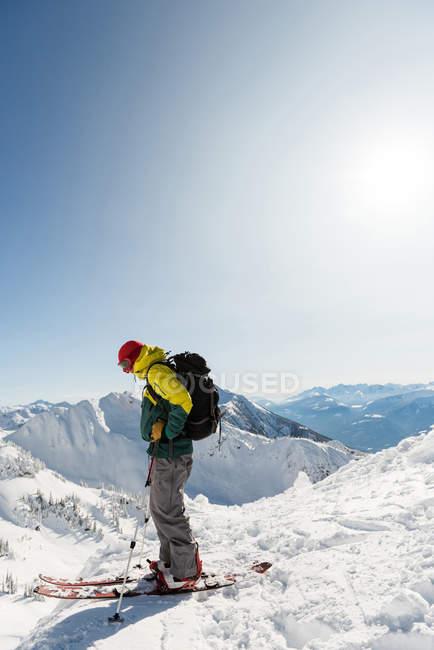 Лыжник, стоя на снежные горы в зимнее время — стоковое фото