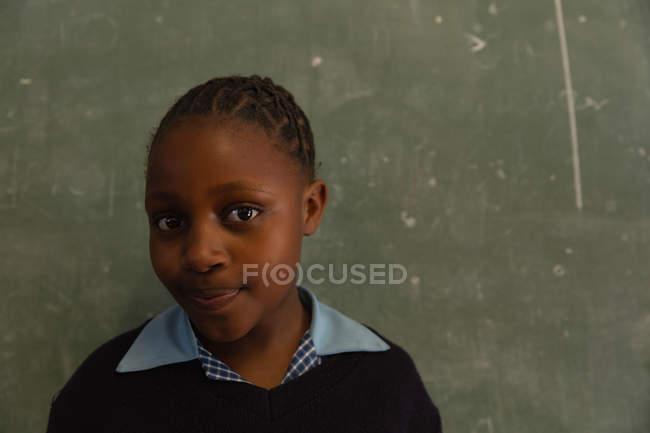 Écolière debout près du tableau dans la salle de classe à l'école — Photo de stock