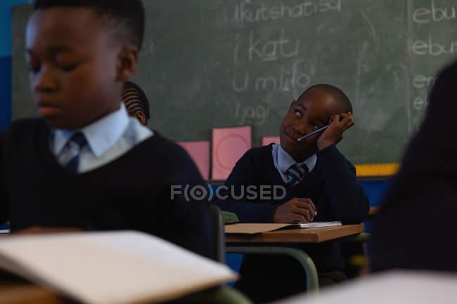 Schoolkid pensif assis dans la salle de classe à l'école — Photo de stock