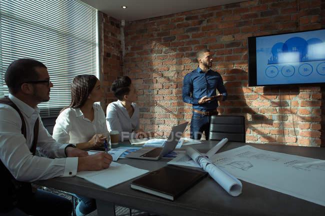 Cadres supérieurs donnant présentation sur écran au bureau — Photo de stock