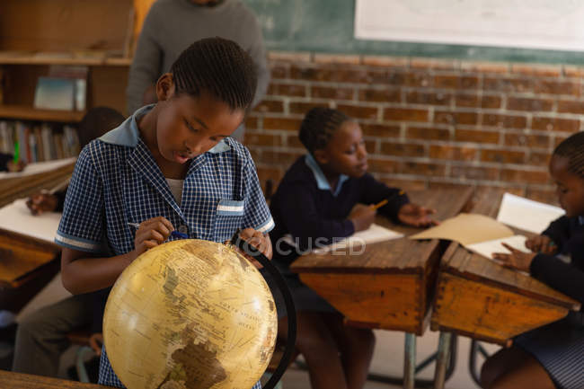 Schoolboy looking at globe in classroom at school — Stock Photo