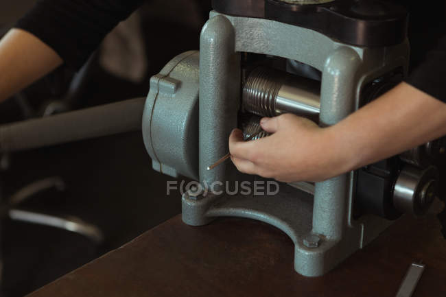 Section médiane de la créatrice de bijoux à l'aide d'une machine en atelier — Photo de stock