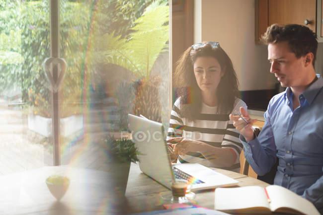 Jovem casal discutindo sobre tablet digital na cozinha em casa — Fotografia de Stock