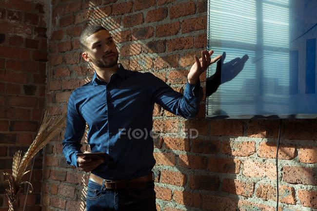 Exécutif donnant présentation sur écran au bureau — Photo de stock