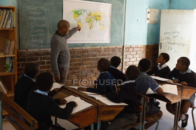 Enseignant de sexe masculin enseigner en classe à l'école — Photo de stock
