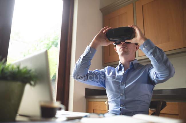 Homme utilisant casque de réalité virtuelle dans la cuisine à la maison — Photo de stock
