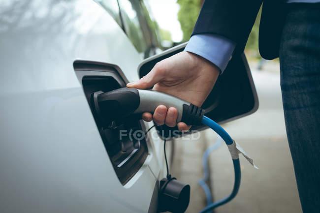 Gros plan d'homme d'affaires, voiture électrique à la station de recharge de charge — Photo de stock