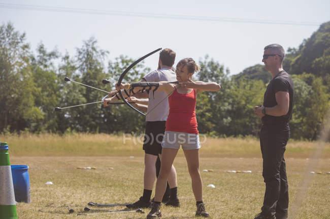 Тренер инструктирует женщину о стрельбе из лука в учебном лагере — стоковое фото