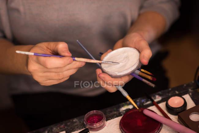 Donna che si dipinge il viso con il pennello per la celebrazione di Halloween — Foto stock