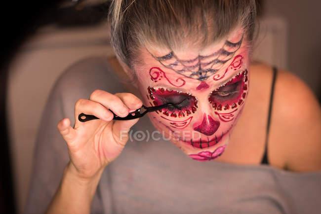 Femme appliquant le mascara sur les yeux pour la célébration de l'Halloween — Photo de stock