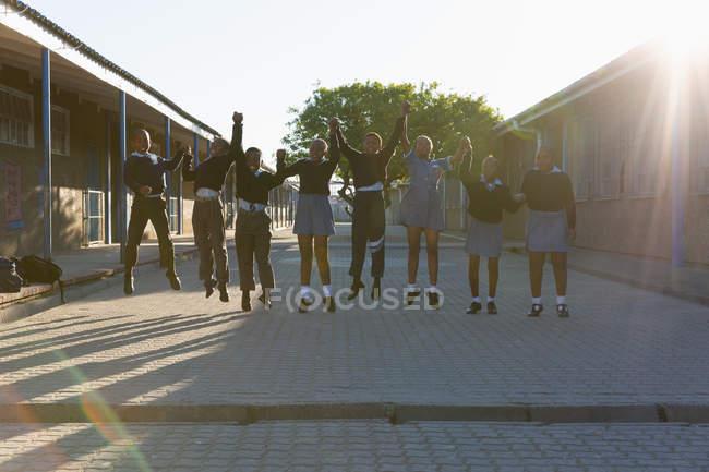 Les écoliers se tiennent la main sur le campus de l'école par une journée ensoleillée — Photo de stock