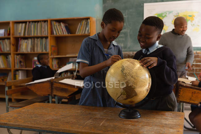 Schoolkids looking at globe in classroom at school — Stock Photo