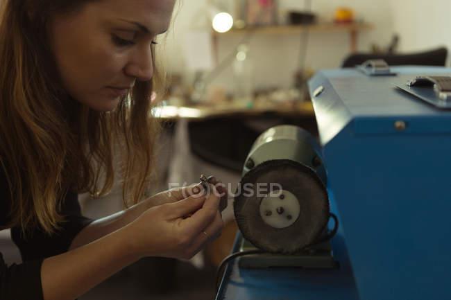 Schmuckdesignerin mit Schärfmaschine in Werkstatt — Stockfoto