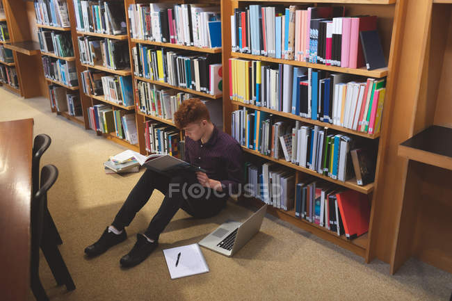 High angle view of college student reading a book in library — Stock Photo