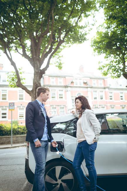 Молодий бізнес колег зарядки електричний автомобіль в зарядний — стокове фото