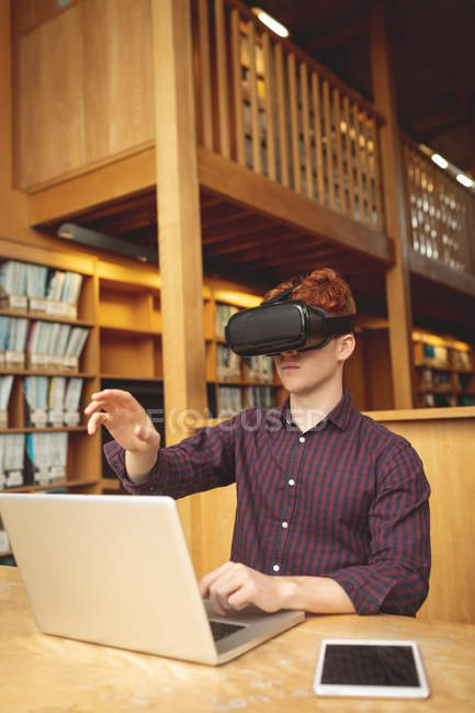 College student using laptop and virtual reality headset in library — Stock Photo
