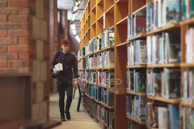 Junge Studentin mit Bücher in die Bibliothek gehen — Stockfoto