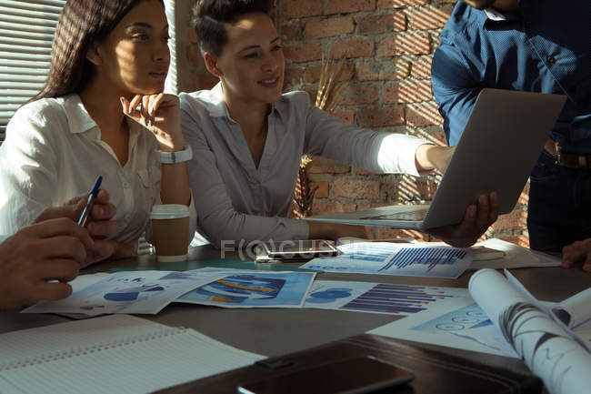 Executives discussing over laptop in conference room at office — Stock Photo