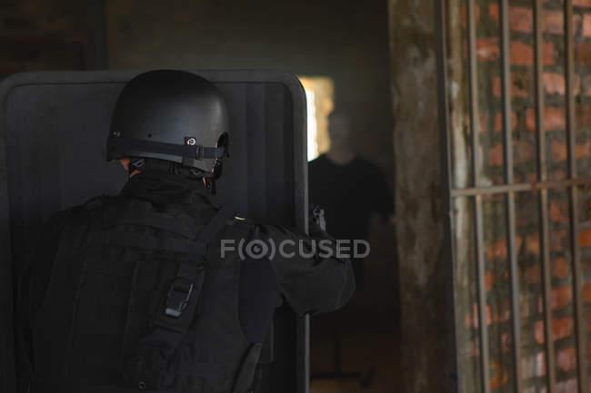 Вид сзади военных солдата, стоя с щитом во время военной подготовки — стоковое фото