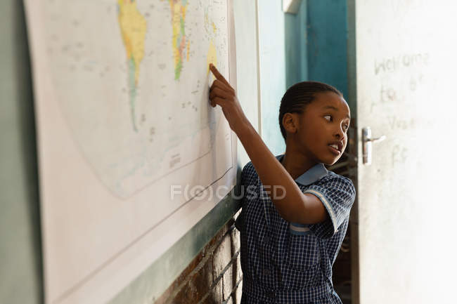 Schoolboy explaining about world map in classroom at school — Stock Photo