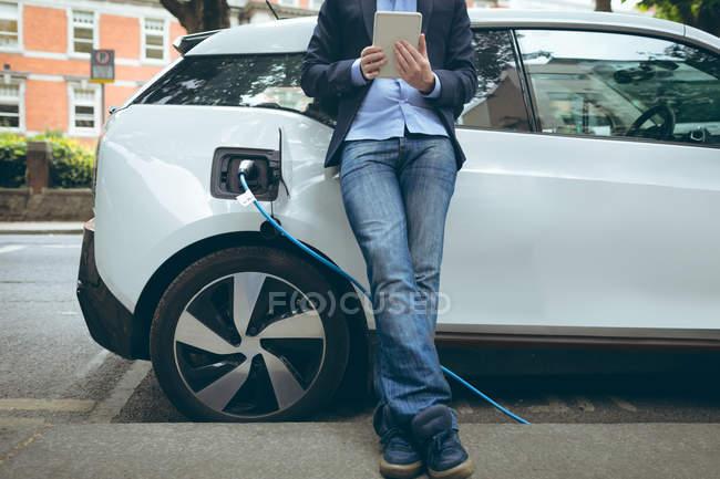 Низкая часть бизнесмен, с использованием цифровых таблетки во время зарядки электромобилей на зарядная станция — стоковое фото
