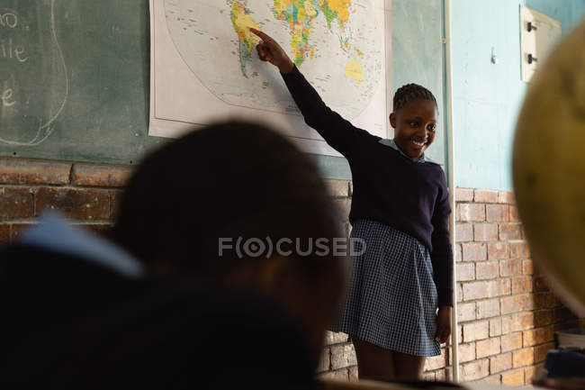Schoolgirl explaining about world map in classroom at school — Stock Photo