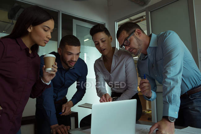 Executives discussing over laptop in office — Stock Photo